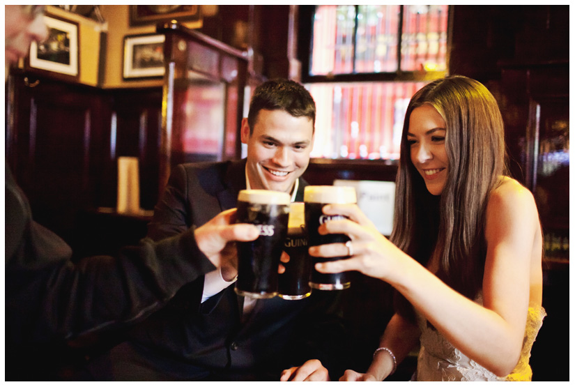 bride and groom toast with pints of Guinness at the famous Temple Bar in downtown Dublin Ireland